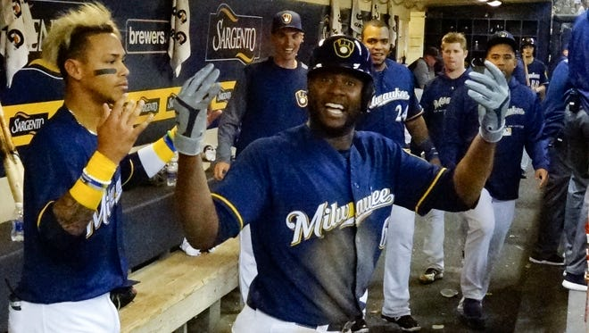 Lorenzo Cain celebrates his leadoff home run against the Marlins in the bottom of the fifth inning in the Brewers' dugout as teammates look on.