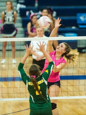 Bison player Amelia Longin spikes the ball past Rustler Josey Quinn during the Crosstown volleyball game at Great Falls High.