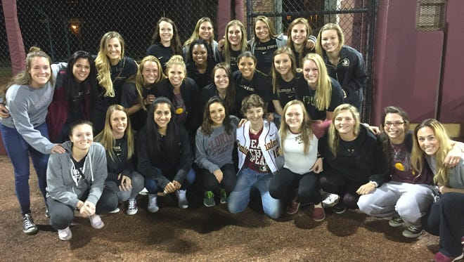 Madison Marshall (white jersey) poses with members of the Florida State softball team.