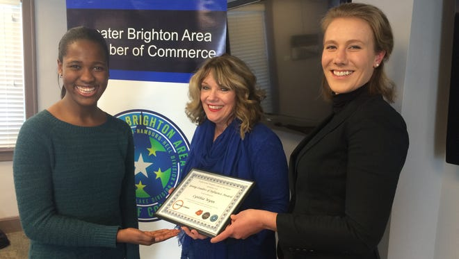 Brighton High School senior Cynthia Wynn, left, receives the Young Leaders of Influence Award from Pam McConeghy, center, and Catherine Daniel.