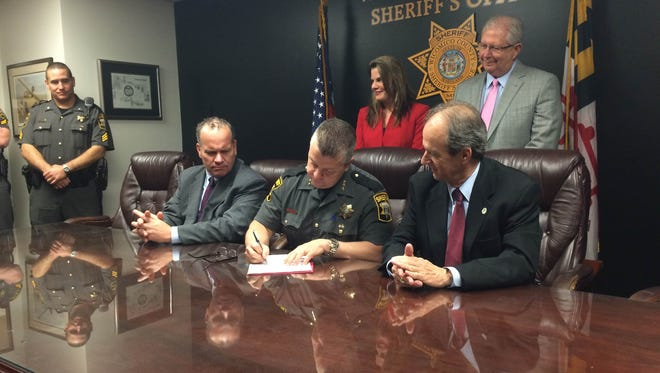 Wicomico County Sheriff Mike Lewis signs a collective agreement contract Thursday April 28, 2016.