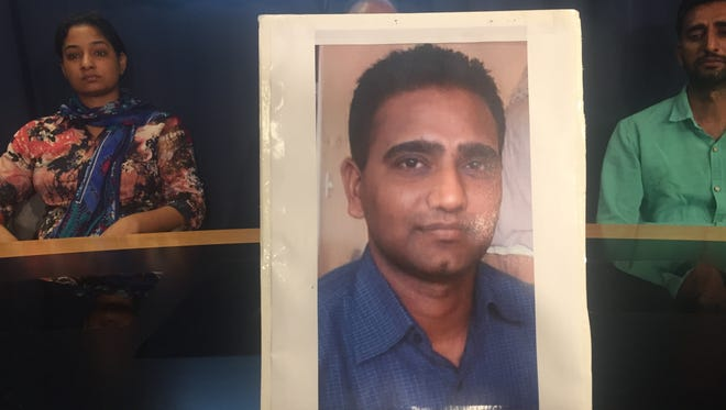 A picture of Amanjeet Toor, 36, is held up by family members at a press conference hoping to help find Toor's killer, Thursday, Aug. 11, at the Phoenix Police Department. His wife, Kamaldeep Kaur, is on the left.