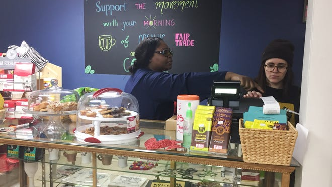 Ebony Nyoni, left, founder of Black Lives Matter Vermont, works on Saturday with Emma Redden, a volunteer at the new Shop 4 Change store and safe-space in Winooski. Photographed Feb. 11, 2017.