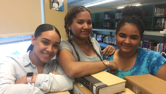 Ana Santos, 15, (center) will graduate Vineland High School Wednesday thanks to her hard work and support from fellow graduates, her cousin, Cynthia Estevez, 18, (left) and her sister, Mayorix Santos, 18 (right).
