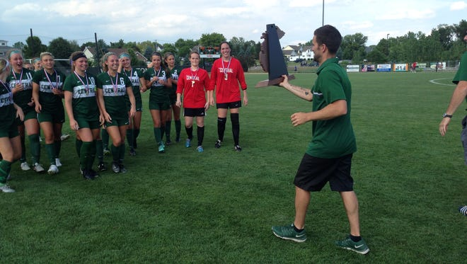 Grand Rapids Forest Hills Central girls soccer coach Jeremy Stacy gets ready to hand his team the Division 1 state championship trophy following a 2-0 win over Grand Blanc on Saturday, June 17, 2017 at Williamston High School.