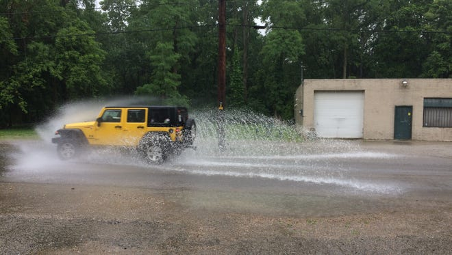 A Jeep splashes through standing water on Bridge Avenue early Friday afternoon.