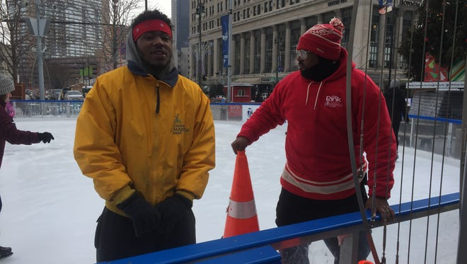 Felix Davis, 22, and Ron Edwards, 41, both of Detroit, endure freezing cold temperatures while working at Campus Martius Park ice skating rink in downtown Detroit. January 2018 photo