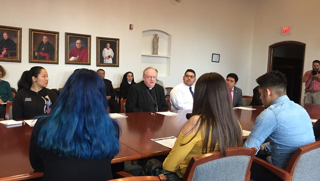 """Bishop Dennis Sullivan (center) speaks with Dreamers about a nationwide call-in campaign to urge """"common sense, humane"""" action on immigration reform."""