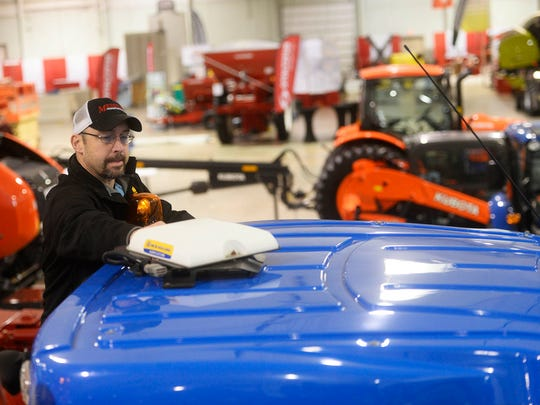 Tom Wagner, precision farming specialist for Messick's Farm Equipment, installs the receiver on to  a 4-wheel drive tractor. The receiver receives satellite signal to guide the equipment.