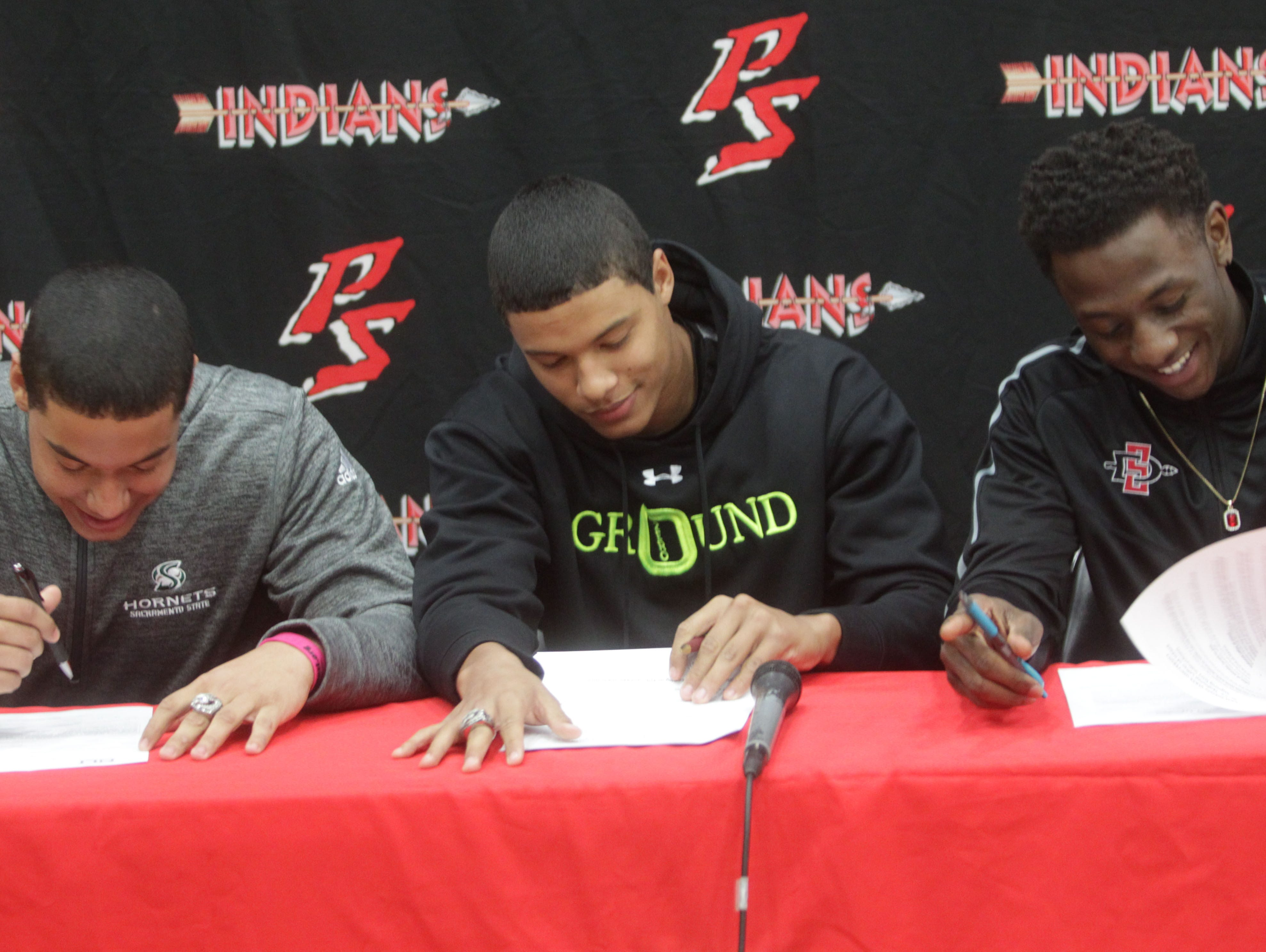 From left, twins, Tyler and Tayler Hawkins and Trenton Thompson, all students of Palm Springs High School sign their letter of intent to attend Universities on football scholarships. Tyler will attend Sacramento State University of California and Tayler and Trenton will attend San Diego State University.