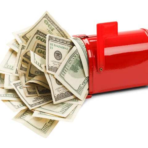An open red mailbox with a bunch of 100-dollar...