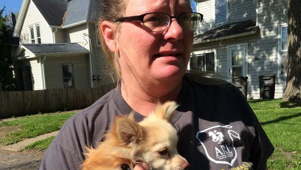 Animal Rescue League of Iowa Officer Tina Updegrove holds Pugsy on Wednesday after the dog was found shaking after a house fire.