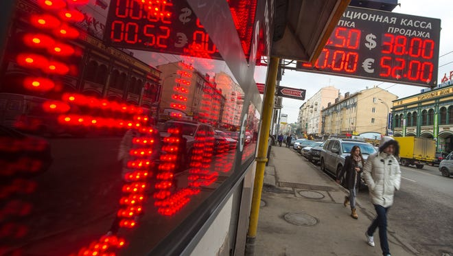 People walk under under a board listing foreign currency rates against the Russian ruble just outside an exchange office in central Moscow on March 3.