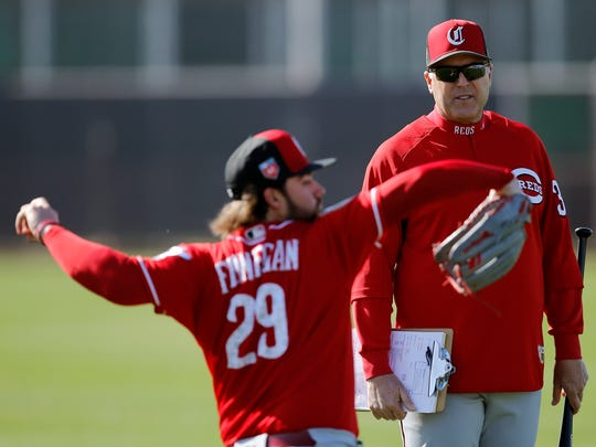 Cincinnati Reds manager Bryan Price (38) talks with starting pitcher Brandon Finnegan (29) as he warms up during practice at the Cincinnati Reds training complex in Goodyear, Ariz., on Wednesday, Feb. 21, 2018.