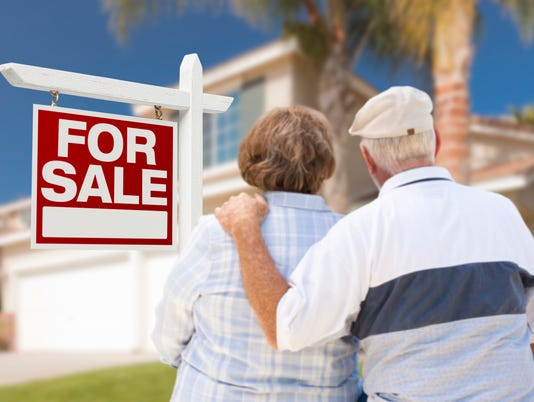 Senior Couple Front of For Sale Sign and House