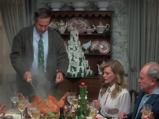 Clark Griswold cuts into the turkey during Christmas dinner in 'National Lampoon's Christmas Vacation'.
