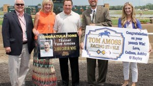 Tom Amoss, center, in the ceremony congratulating the trainer on his 3,000th win. Amoss' wife, Colleen, is helping to hold up the sign. At right is a sign made by the Amoss' daughters, Hayley and Ashley, who were not able to attend.