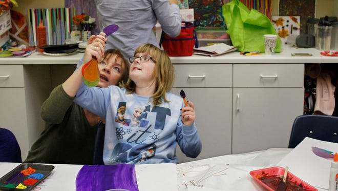 Art teacher Kate Clemont goes over color samples with Allie Hobbs, 12, Webster, as she paints rainbows in their art therapy class at the new Family Autism Center on University Avenue in Rochester.