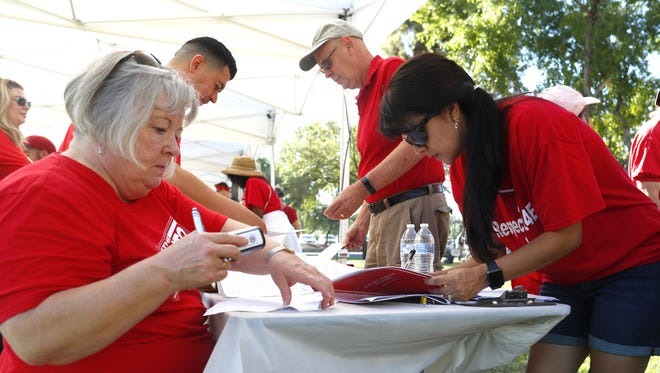 Angela Philpot signs off on her petition signatures gathered with Nell Pederson, left, as RedforEd supporters gather outside the State Capitol in Phoenix on June 23, 2018.