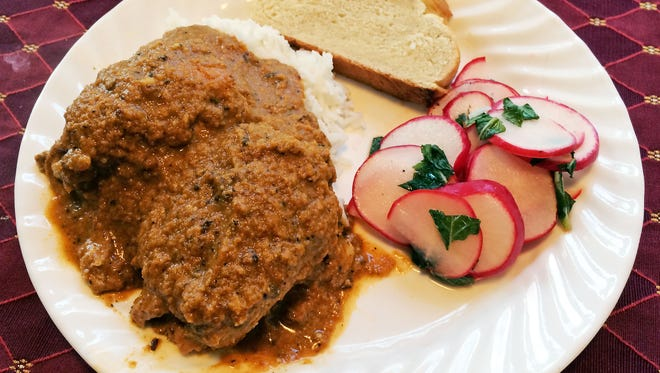 Pepian de pollo is a Guatemalan dish of chicken thighs simmered in a blended sauce.