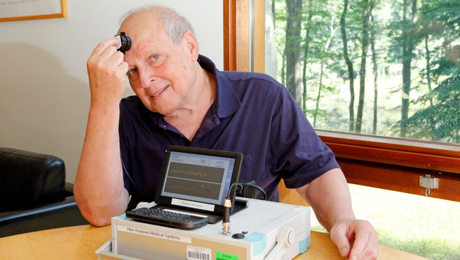 Arthur Rappaport, inventor of a non-invasive device to measure for traumatic brain injury, is photographed July 8 at his home in Pound Ridge. The device has a probe and measures pressure inside the brain.
