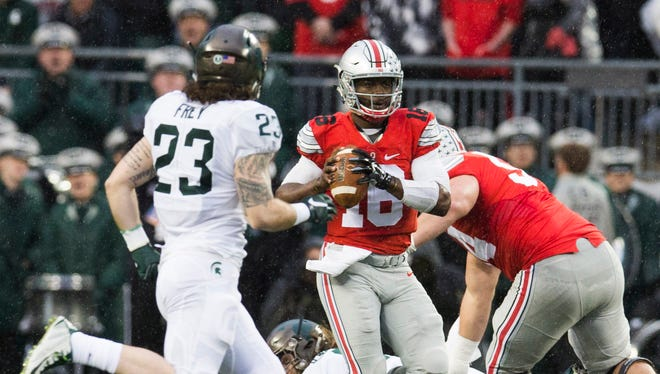 Nov 15, 2015; Columbus, OH, USA; Ohio State Buckeyes quarterback J.T. Barrett (16) looks for an open receiver under pressure from Michigan State Spartans linebacker Chris Frey (23) at Value City Arena.