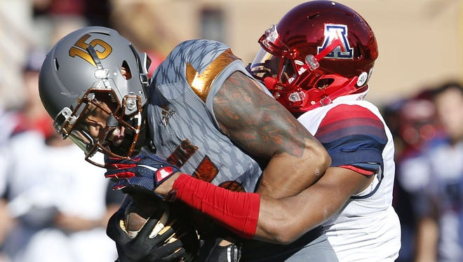 Arizona State wide receiver Devin Lucien, #15, is tackled by Arizona Cam Denson, #3, during the first quarter of Territorial Cup game at Sun Devil Stadium in Tempe on November 21, 2015.