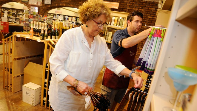 West Meade Wine & Liquor Mart co-owner Frances Anne Varallo and employee Ben Holt hang  bottle bags on a display Monday, June 30. The store is preparing to sell items other than alcohol, including gourmet meats, candies and desserts, thanks to a change in state law.