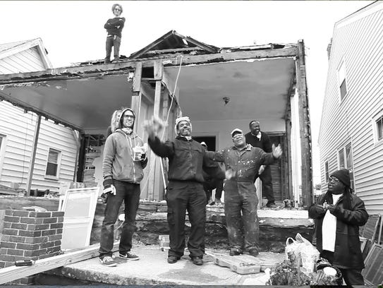 Artist Ryan Mendoza (standing left) and crew demolishing