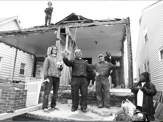 Artist Ryan Mendoza (standing left) and crew demolishing