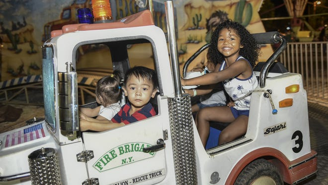 Davin Duenas, 3, of Tamuning, drives a 3rd Battalion rescue truck as Trinity Jackson, 4, of Yigo, contributes to the rescue effort on the Big Truck ride at the Liberation Carnival in Tiyan on June 13.