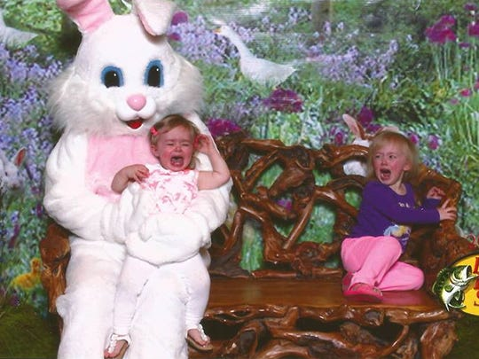 Paetyn, 3, finds a safe corner away from the Easter bunny while Alivia, 20 months, takes her turn on its lap.