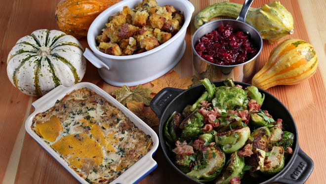 Thanksgiving potluck spread, clockwise from upper right, orange cranberry sauce, brussels sprouts with pancetta, butternut squash gratin, and cornbread stuffing with dried fruit by Chef Patrick Fegan of Tavern Americana as seen in Scottsdale on Nov.7, 2014.