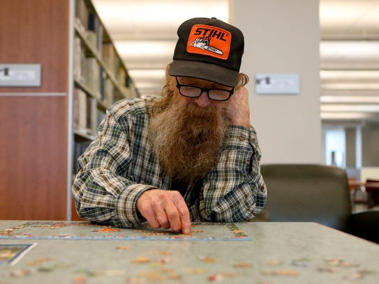 Paul Harper works on a puzzle Wednesday at the Redding