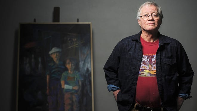 Bruce Preheim, an artist and musician who is fighting cancer, poses for a portrait with one of his paintings Friday  at the Washington Pavilion in Sioux Falls.