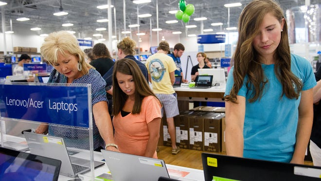 Caroline Head, right, clicks through websites on a laptop at a Best Buy in Augusta, Ga., in August 2014.