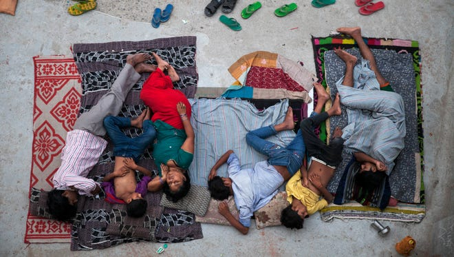 An Indian family sleeps on the roof of a house to beat the heat in New Delhi on May 29, 2015.