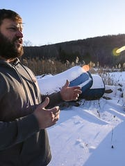 Developer Travis Belisle, seen on Friday, January 22, 2016, is proposing to erect 7 nearly-500 foot high wind turbines on a hill behind his home in Swanton. (The metal tubes behind Belisle have nothing to do with the project).
