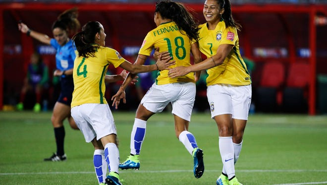 Brazil midfielder Raquel  celebrates with defender Erika and midfielder Beatriz after scoring a goal during the second half against Costa Rica in a Group E soccer match in the 2015 FIFA women's World Cup at Moncton Stadium.