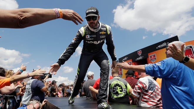 Jimmie Johnson greets fans before a NASCAR Sprint Cup series auto race, Sunday, June 18, 2017, in Brooklyn, Mich.