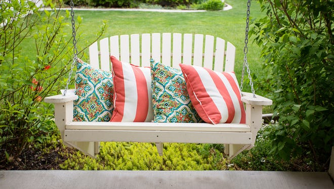 Beautiful wooden front porch swing with comfortable pillows. Outdoor porch seating with lots of green plants and shrubs around it.