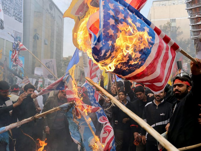 Demonstrators burn U.S. and Israeli flags during a demonstration marking the 34th anniversary of the U.S. Embassy takeover on Nov. 4 in Tehran. Thousands of protesters gathered in front of the former U.S. embassy in Tehran to mark the beginning of the 1979 hostage crisis, burning flags and chanting anti-U.S. slogans.