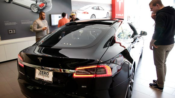 People look at  a Tesla model S in Santa Monica, Calif