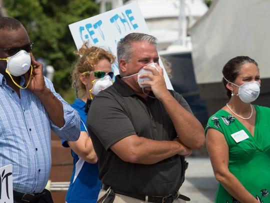 Protesters including (front row, left to right) state Rep. Larry Lee of Port St. Lucie, St. Lucie County Commissioner Chris Dzadovsky and former Sewall's Point Mayor Jacqui Thurlow-Lippisch wear protective masks to listen to U.S. Rep. Patrick Murphy during his visit Sunday, July 10, 2016, at Central Marine in Stuart, the epicenter of that summer's toxic blue-green algae blooms.