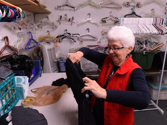 Edna Kopp, a volunteer at the Emilie Center, sorts clothes Tuesday morning at the center, which is designed to help those in need with clothing and household items.