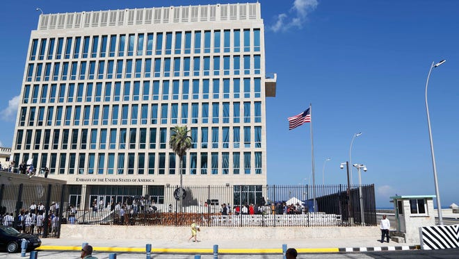 """FILE - In this Aug. 14, 2015, file photo, a U.S. flag flies at the U.S. embassy in Havana, Cuba. Senior U.S. officials say the United States is pulling roughly 60 percent of its staff out of Cuba and warning American travelers not to visit due to """"specific attacks"""" that have harmed U.S. diplomats."""