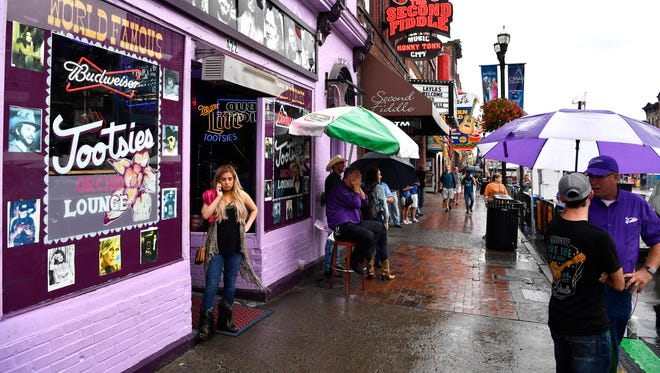 People wait for the rain to stop before the start of Tootsie's 57th Anniversary Birthday Bash on Lower Broadway Tuesday, Oct. 10, 2017 in Nashville, Tenn.