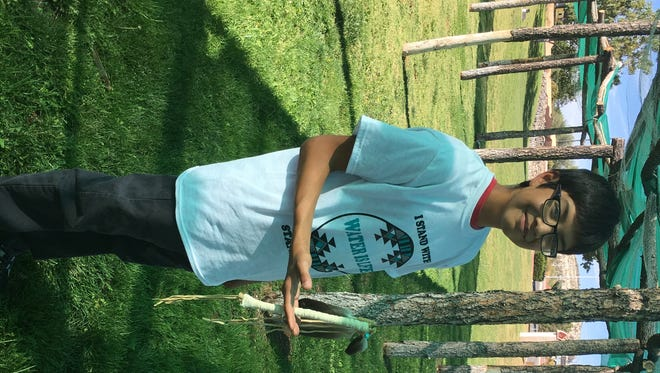 Riley Ortega holds a traditional relay staff given to him by a Yavapai-Apache religious leader.