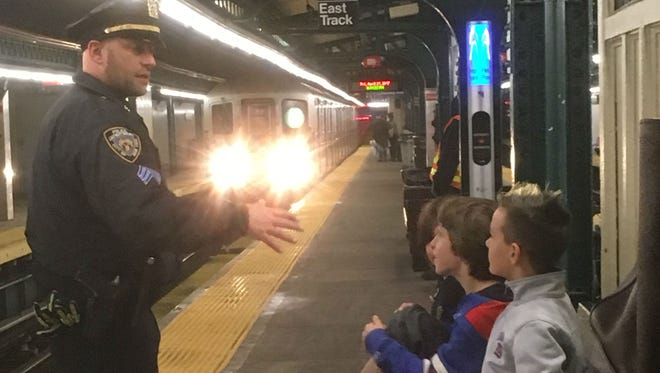NYPD Sergeant Carlos Bernard escorts Little Tor Elementary School students  Dennis Bernard, Coca Bernard and Hudsyn Pincus to the New York City subway to distribute care packages to homeless people Friday, April 21, 2017.