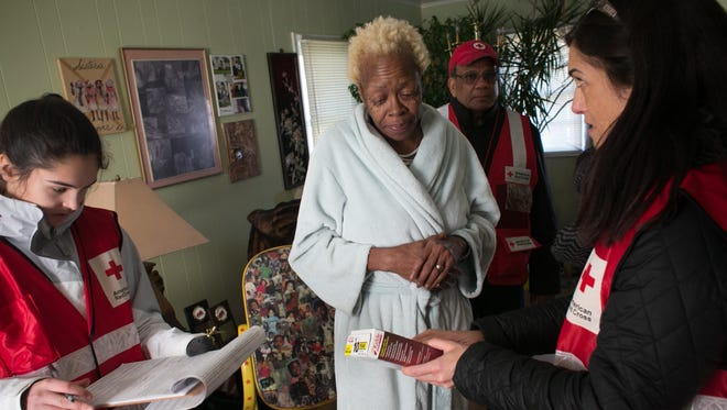 Red Cross volunteers, Grace Godes and Jodi Long give Denyse A. Bennett  a fire alarm and share home fire preparedness and prevention information at her home in District Heights, Md, Jan 18, 2016.